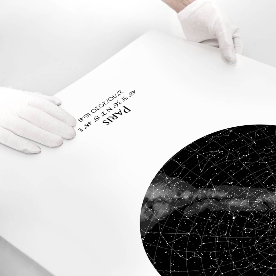 Une personne portant des gants blancs présente une affiche fine art luxe Mundi représentant une carte du ciel personnalisée