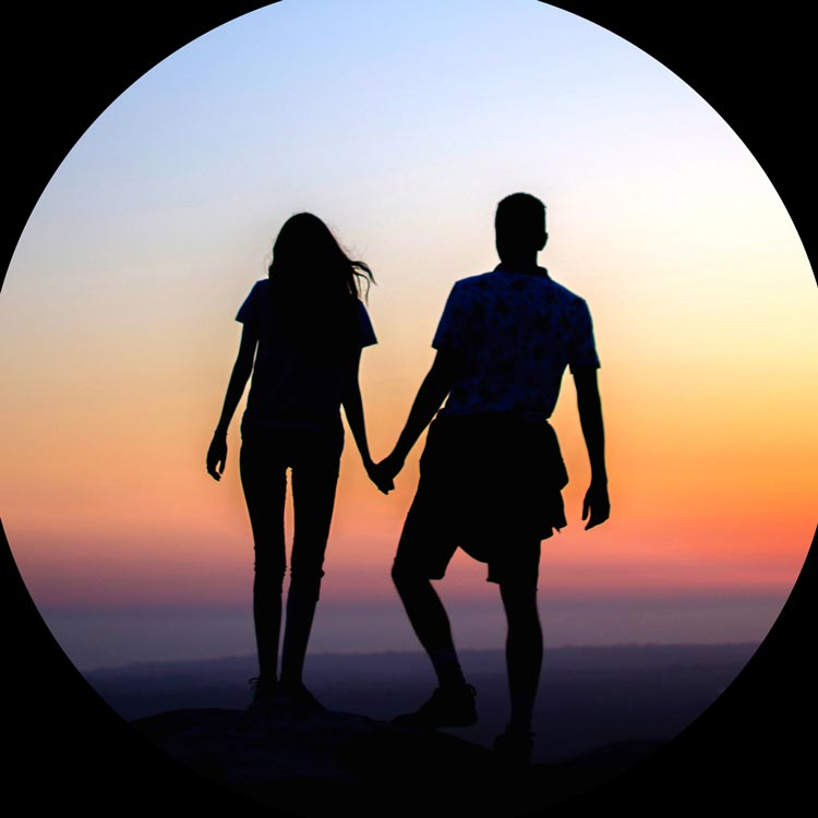 Un homme et une femme se tiennent la main devant un coucher de soleil