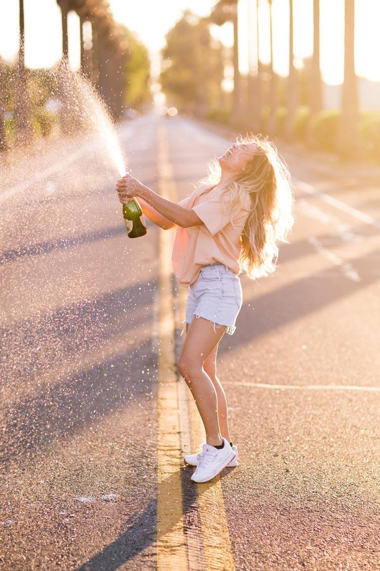 Une jeune fille joyeuse fait gicler une bouteille de champagne
