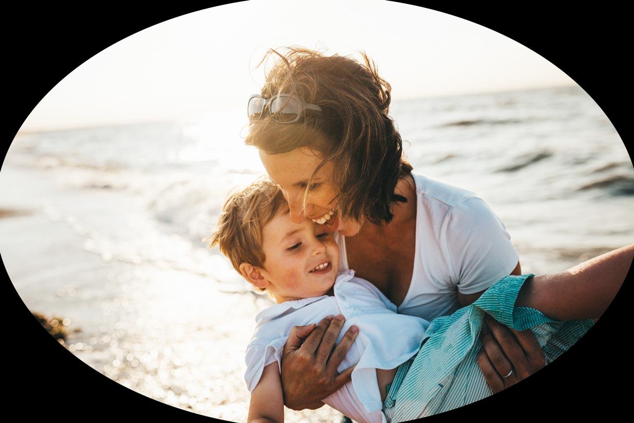 Une femme porte son fils dans ses bras et ils rigolent sur la plage