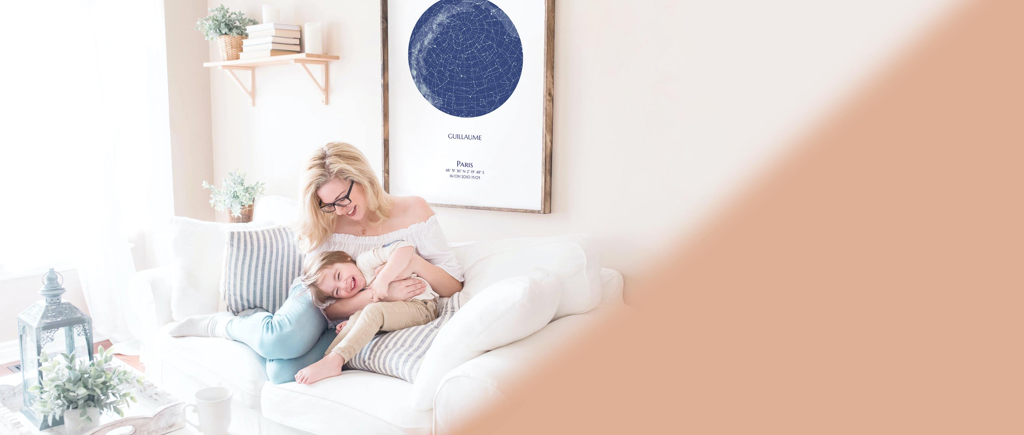 Carte des étoiles personnalisée accrochée au mur au dessus d'un canapé où une femme joue avec son fils