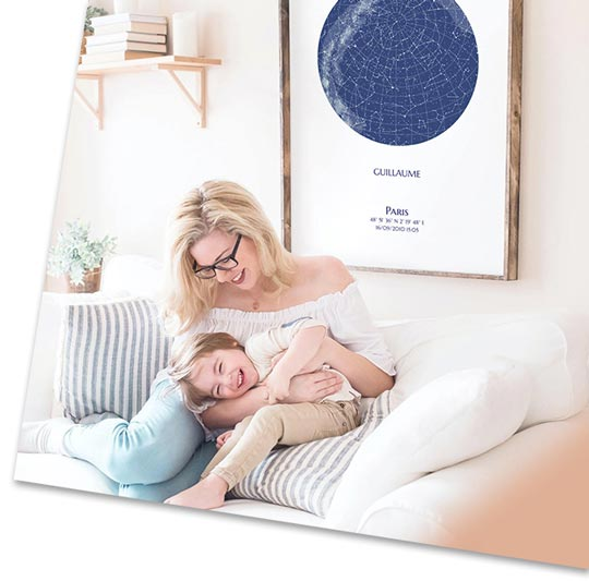 Starmap personnalisée disposée au mur d'un salon où une femme joue avec son fils
